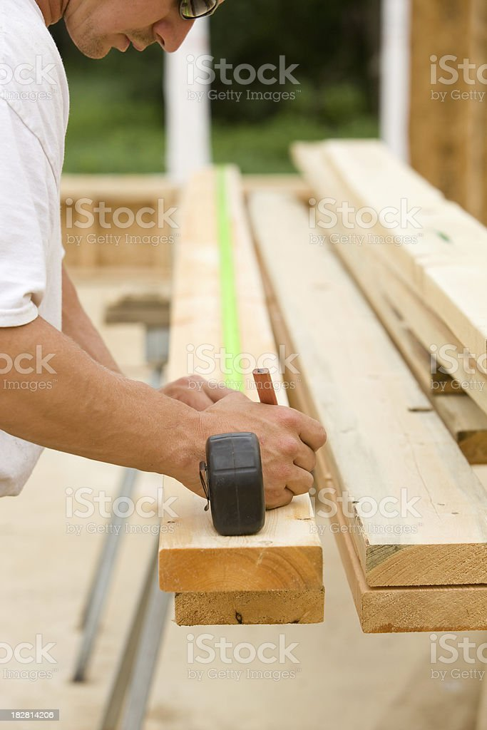 Construction Worker Measuring Board for a New House Frame stock photo
