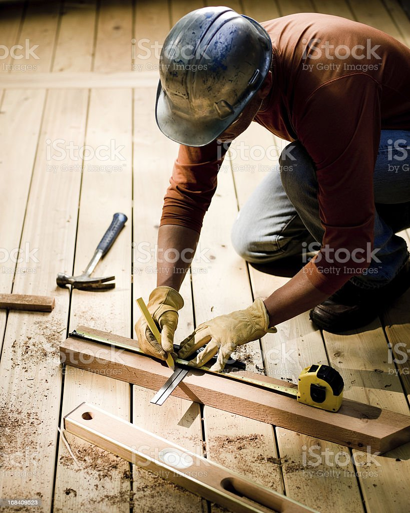 Construction Worker Measuring Lumber stock photo