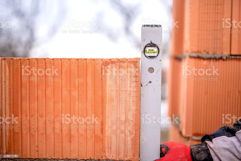 Construction worker measuring with professional level the bricks on walls stock photo