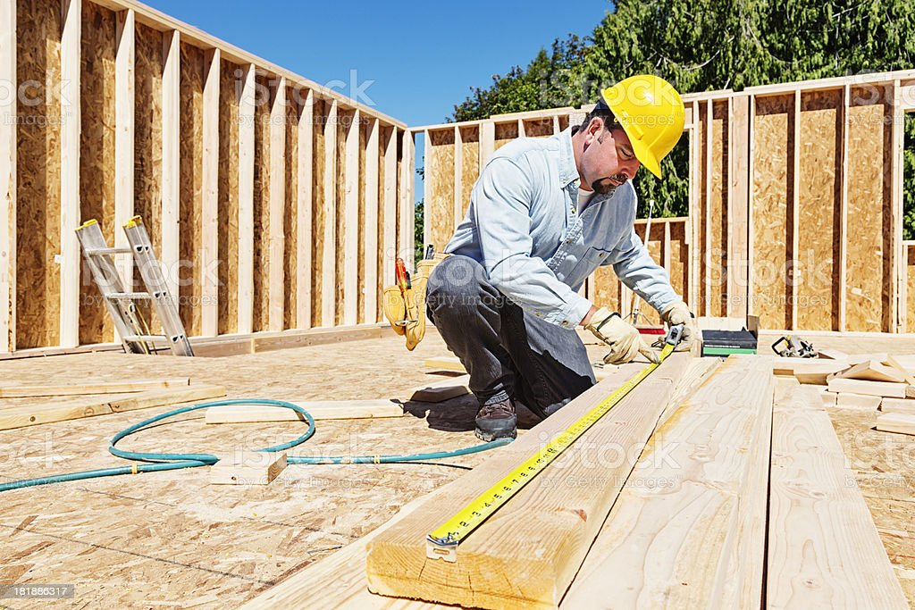 Construction Worker Measuring Wood Beam with Tape Measure royalty-free stock photo