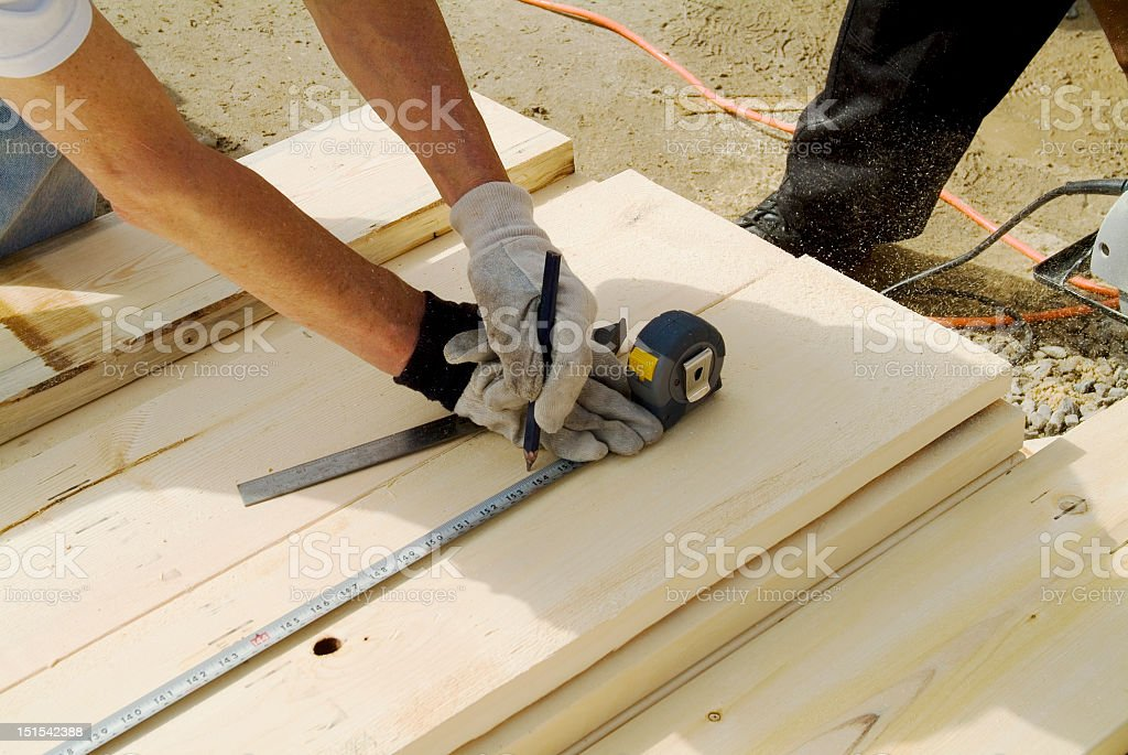 Construction Worker Measuring Wood stock photo