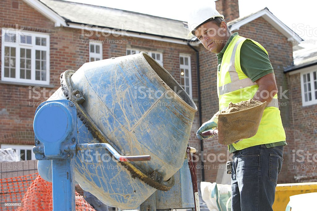 Construction Worker Mixing Cement stock photo