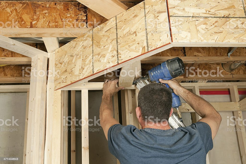 Construction Worker Nailing Ceiling Board stock photo