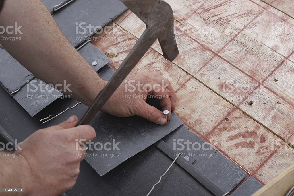 Construction worker nailing roof plaques stock photo