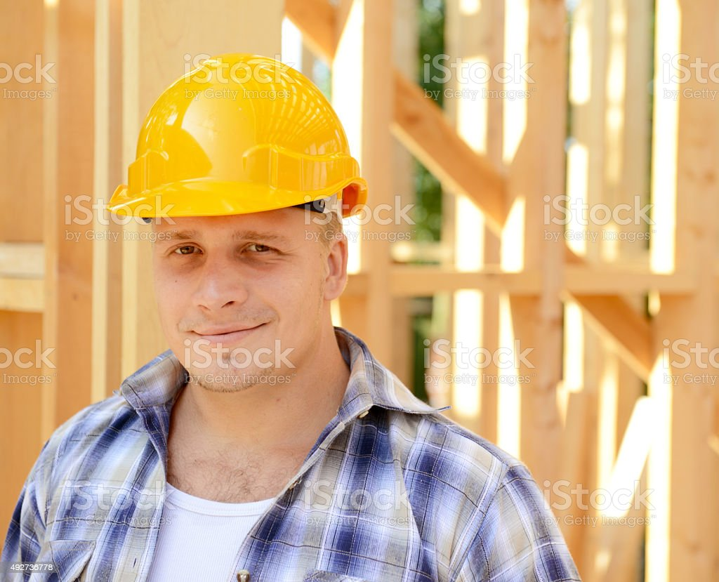 construction worker on a background of a frame house stock photo