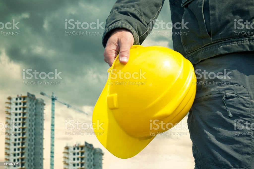 Construction worker on a construction site with a yellow helmet stock photo