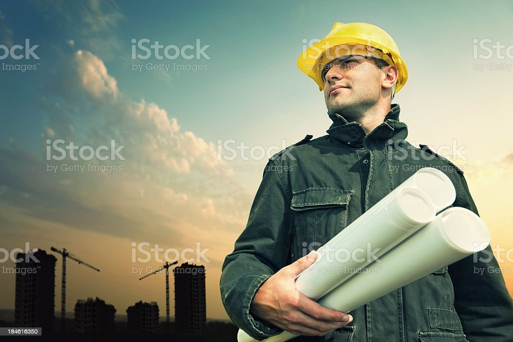 Construction worker on a construction site with blue prints. royalty-free stock photo