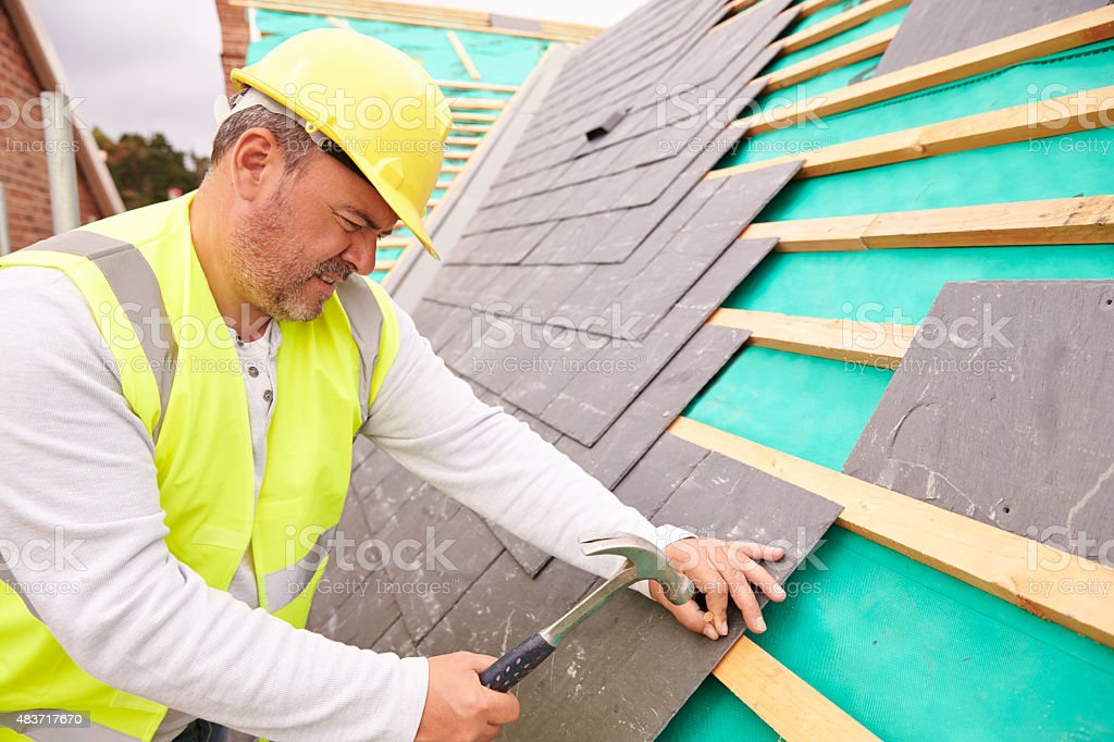 Construction Worker On Building Site Laying Slate Tiles stock photo