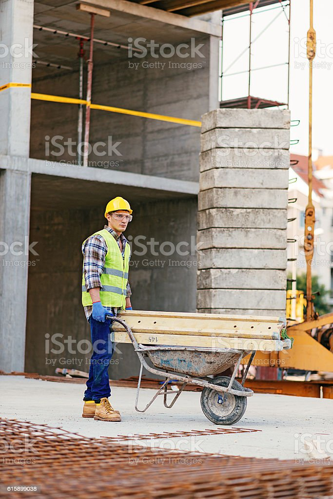 Construction worker on construction site with wheel barrow stock photo