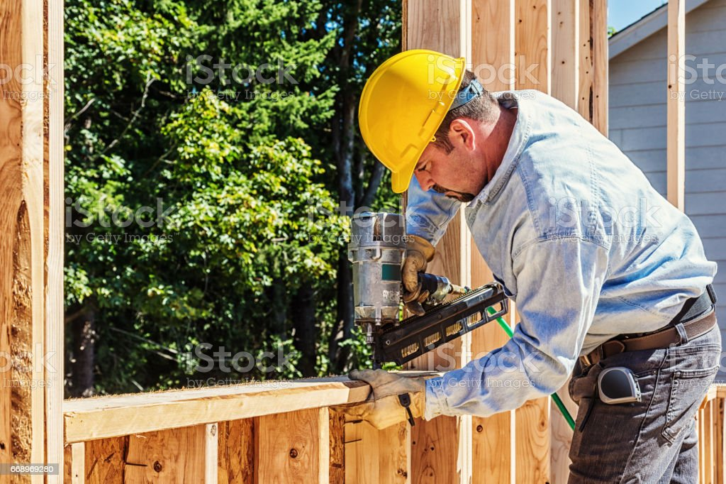 Construction Worker on Site with Nail Gun stock photo