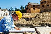 Construction Worker on Site with Plans