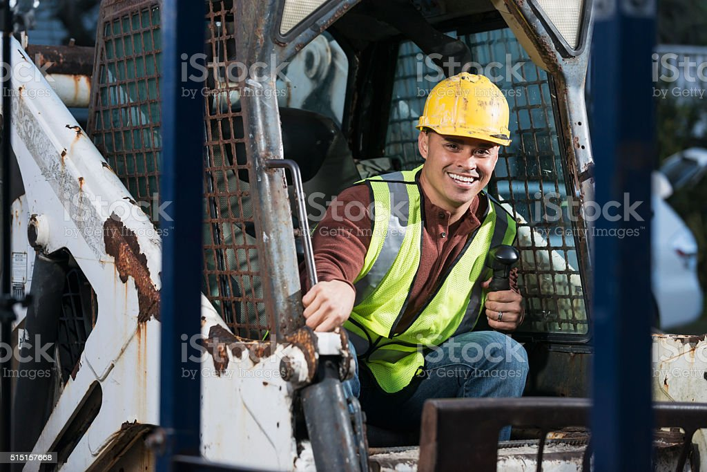 Construction worker operating a back hoe stock photo