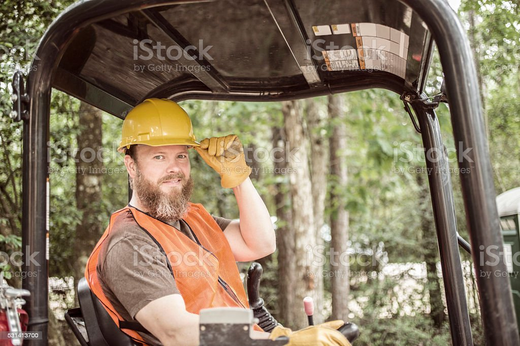 Construction worker operating bulldozer at job site. stock photo