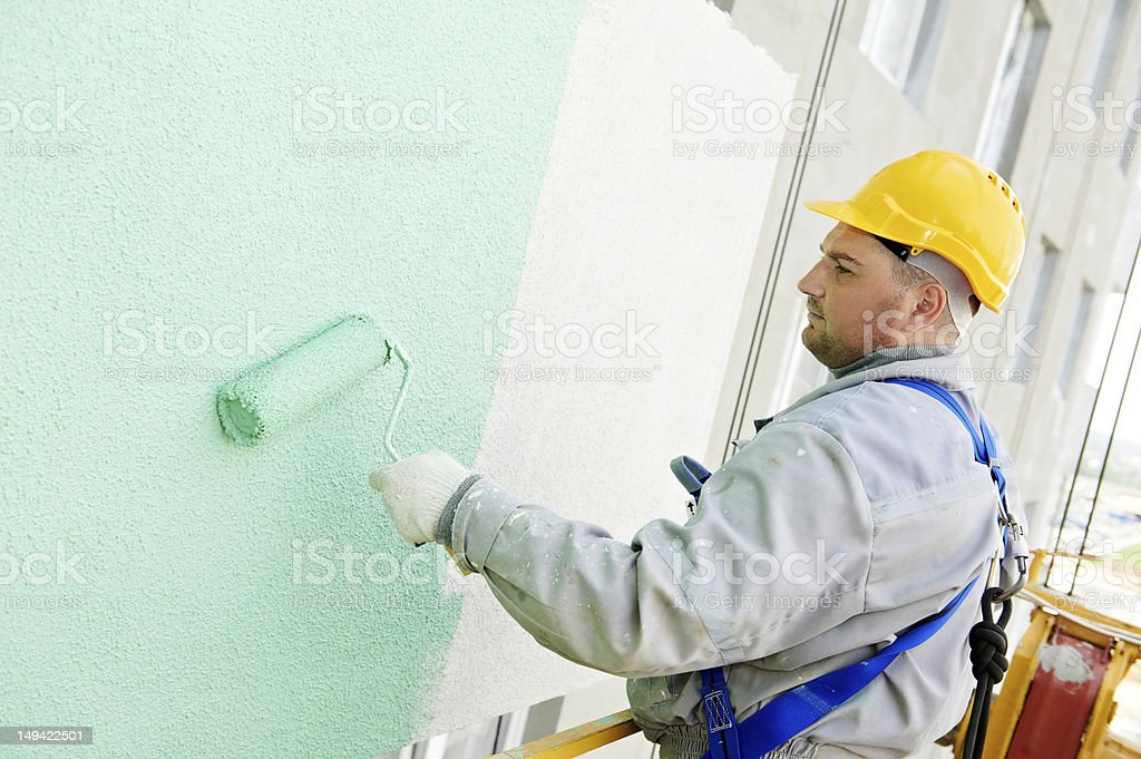 Construction worker painting building facade with green tone royalty-free stock photo