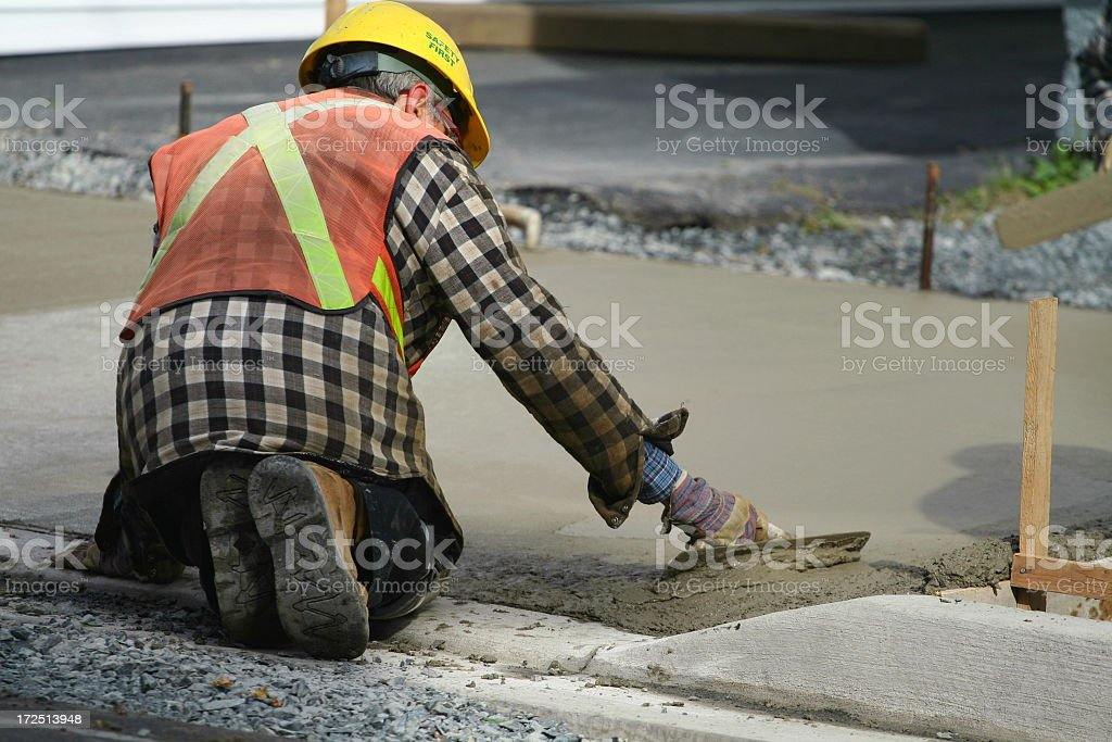 A construction worker paving the sidewalk with concrete royalty-free stock photo
