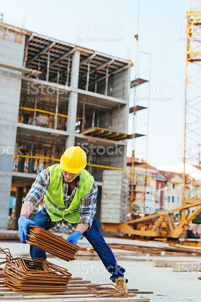 Construction worker picking up steel rods for armature stock photo