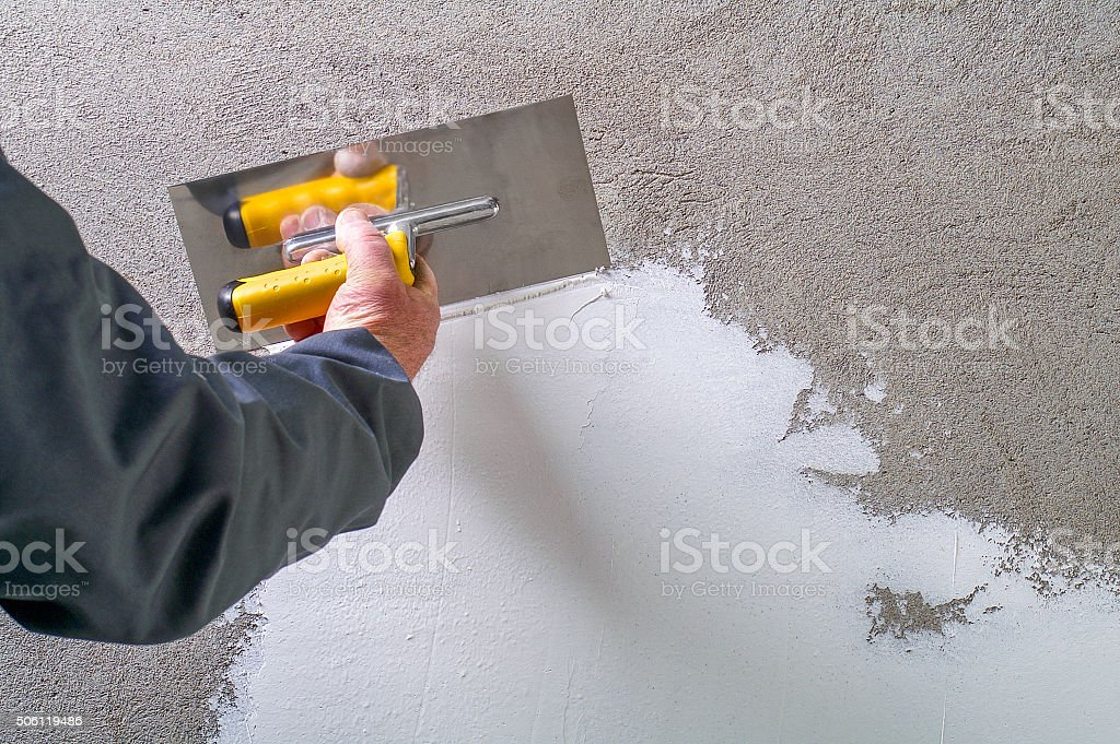 Construction worker - plastering and smoothing concrete wall stock photo