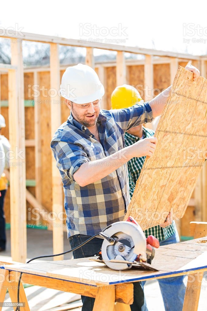Construction worker prepares board to be cut at job site stock photo