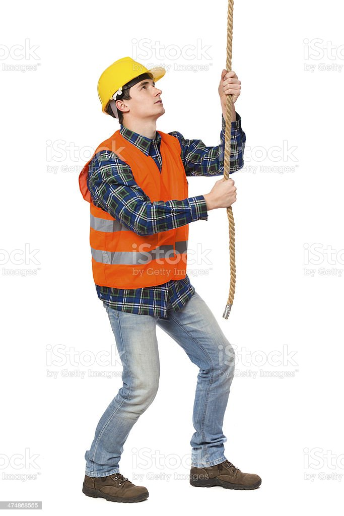 Construction worker pulling a rope. royalty-free stock photo