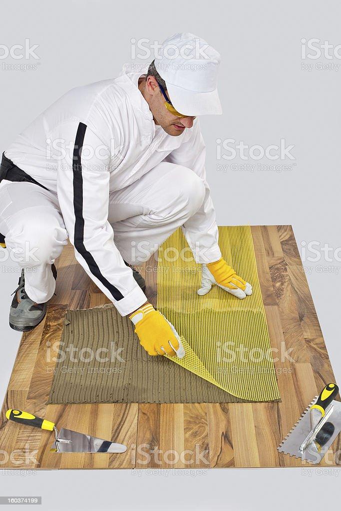 Construction worker put fiberglass mesh on tiles adhesive wooden floor stock photo