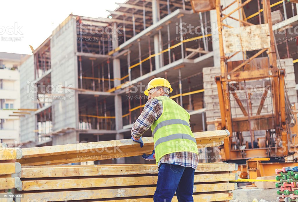 Construction worker putting planks on pile near crane stock photo