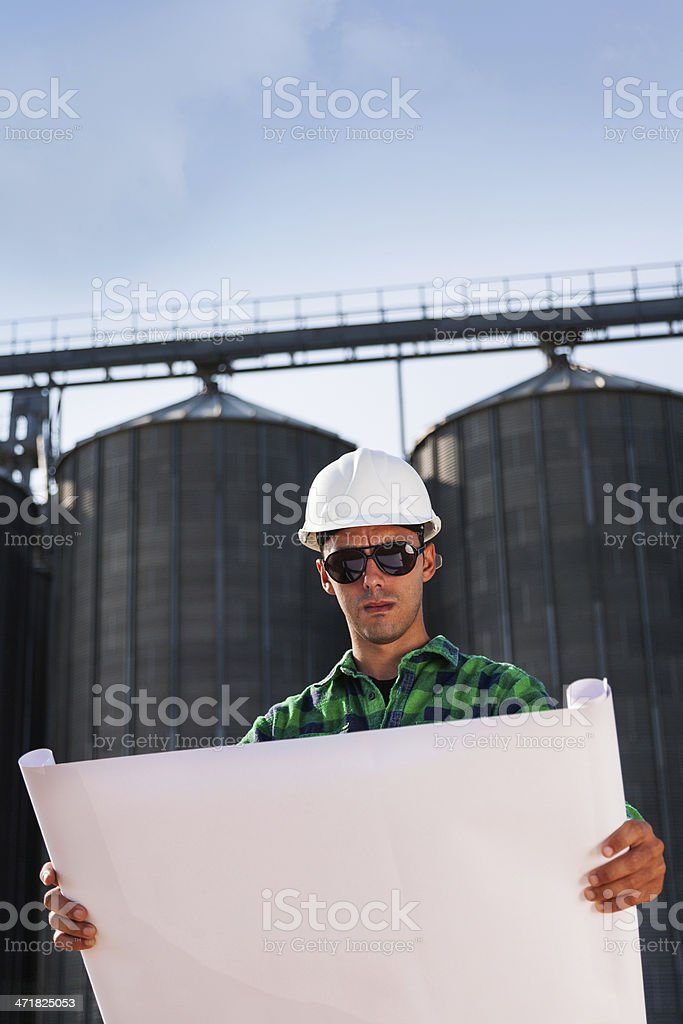 Construction worker reading blueprint royalty-free stock photo