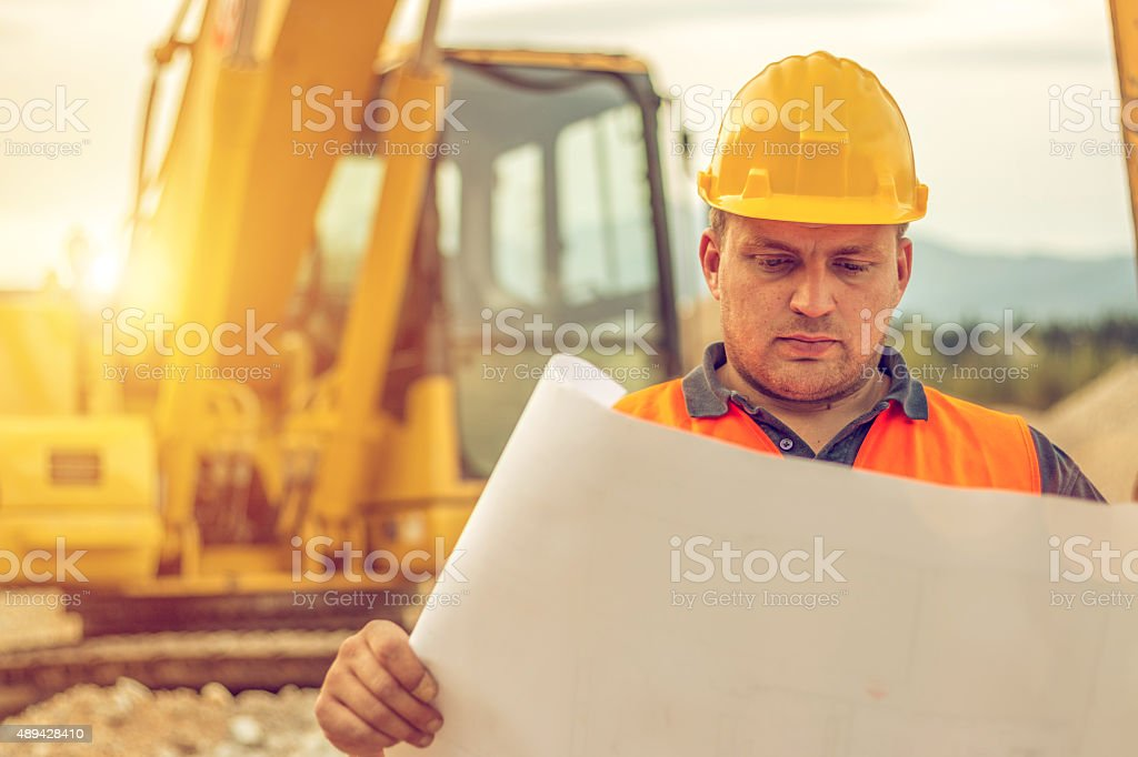 Construction worker reading blueprints stock photo