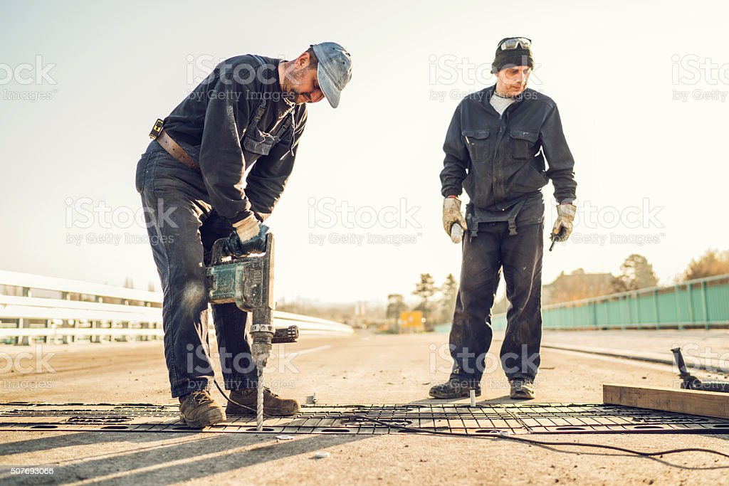 Construction worker repairing bridge with a drill. stock photo