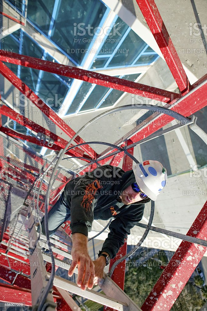 Construction worker scales high rise red crane ladder stock photo