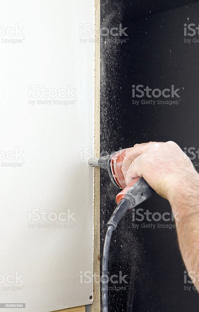 Construction Worker Screwing Sheetrock to a Wall Stud. stock photo