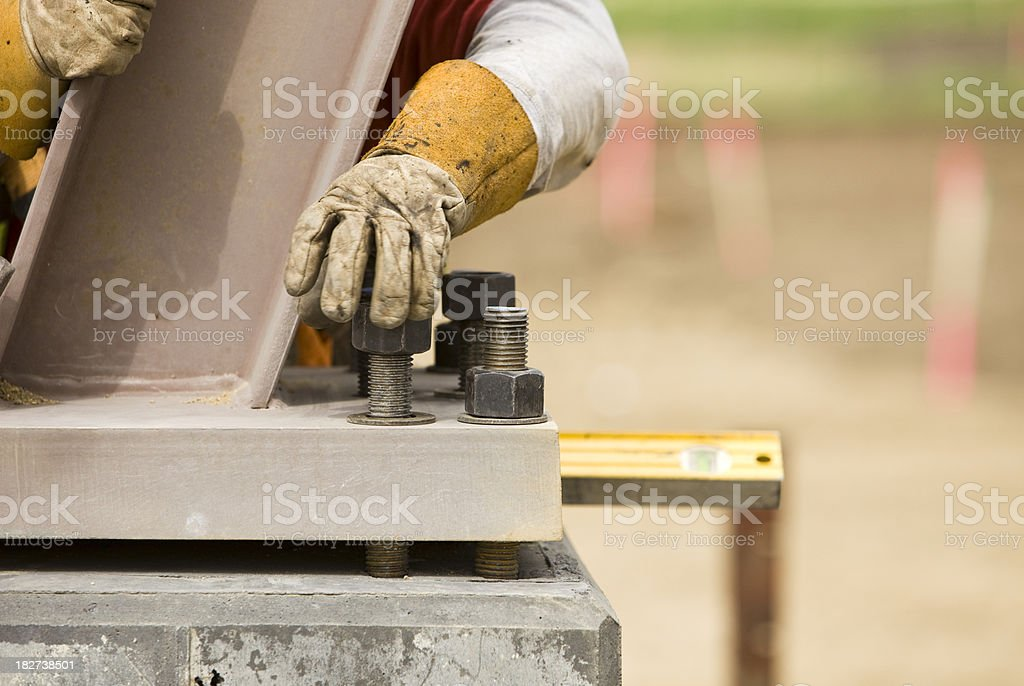 Construction Worker Securing Support Column with a Nut royalty-free stock photo