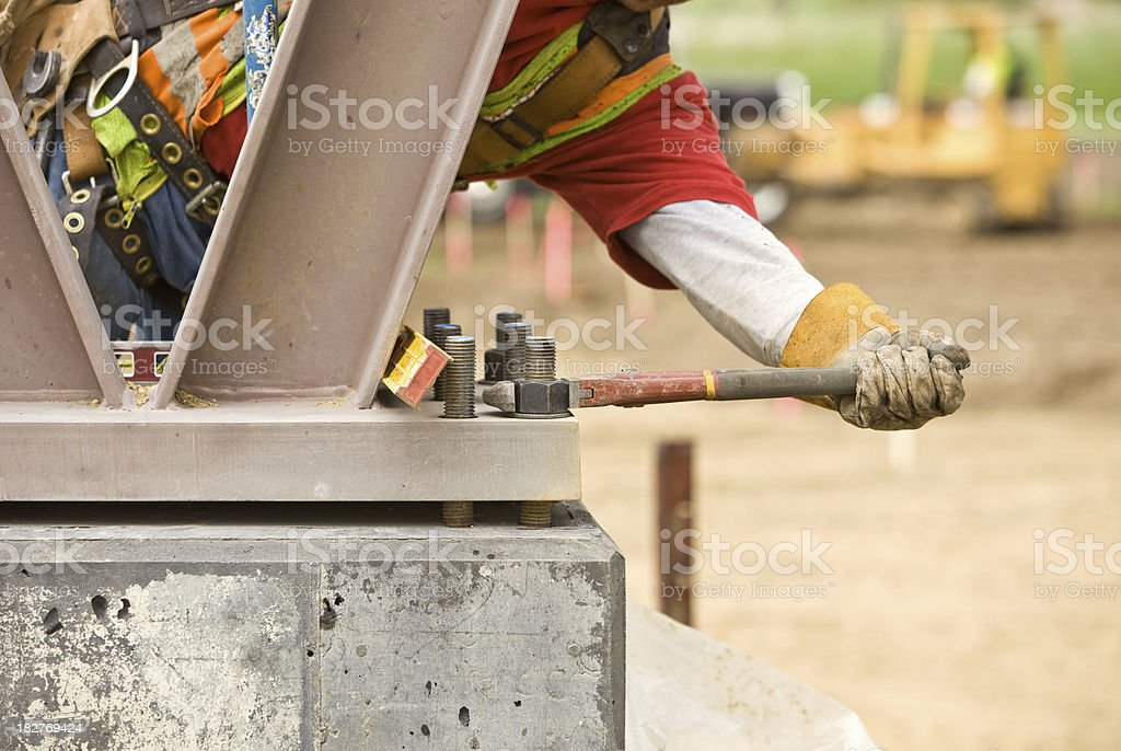 Construction Worker Securing Support Column with a Pipe Wrench stock photo