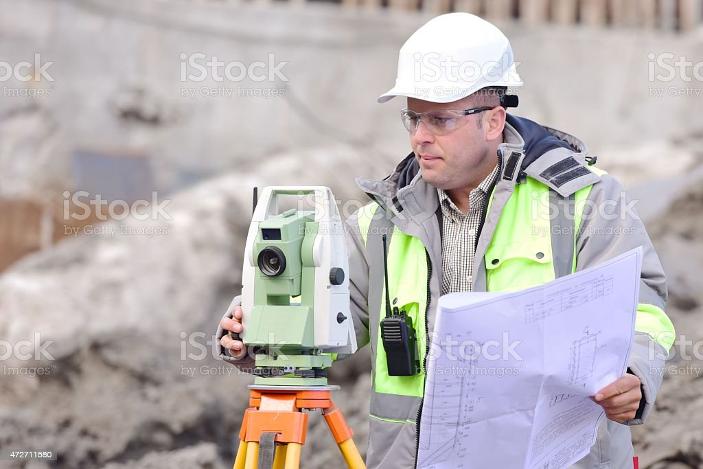 A construction worker setting up a camera at a site stock photo