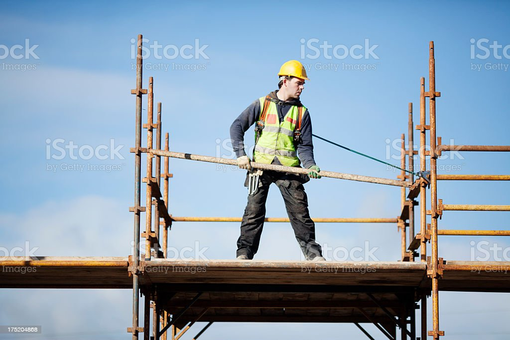 Construction worker setting up scaffolding against the sky stock photo