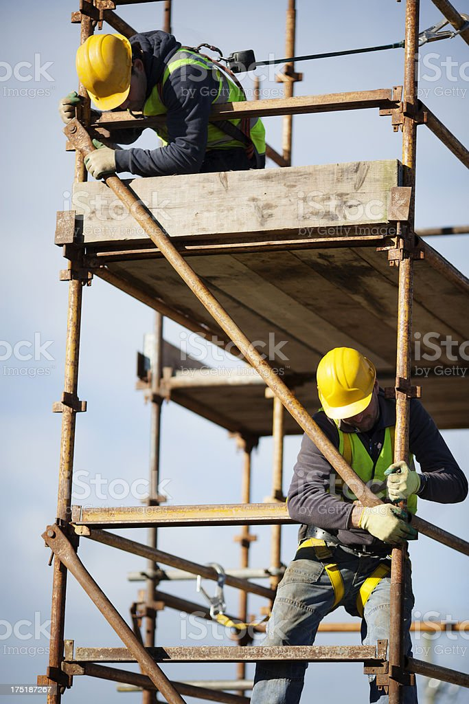 Construction worker setting up scaffolding stock photo