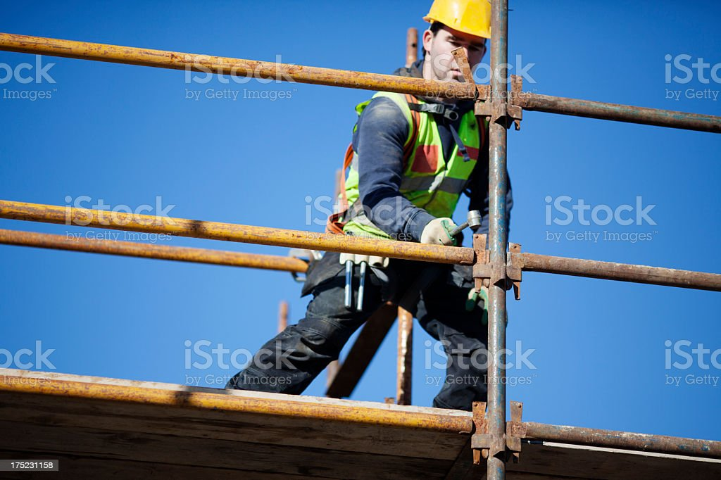 A construction worker setting up scaffolding stock photo