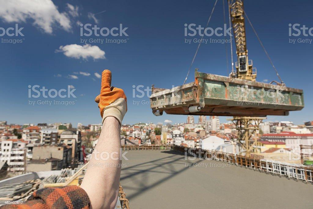 Construction worker signaling to crane operator stock photo