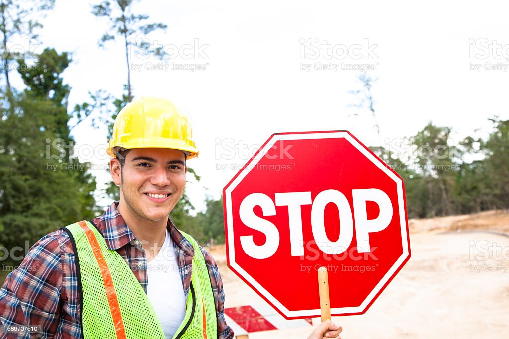 Construction worker, signalman holds stop sign at job site. stock photo