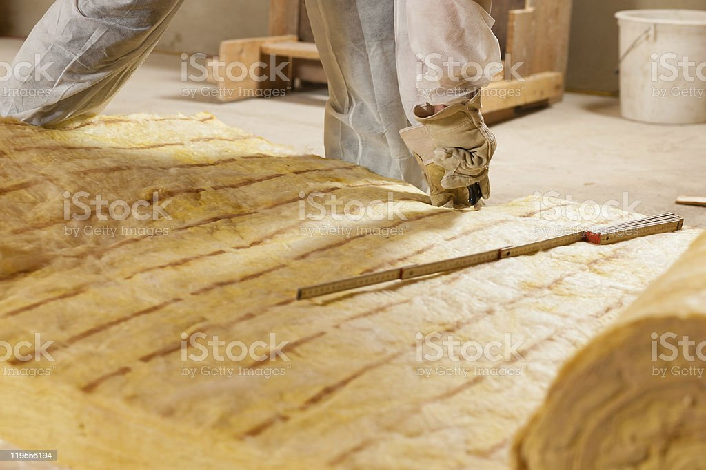 Construction worker slicing material used for insulation stock photo
