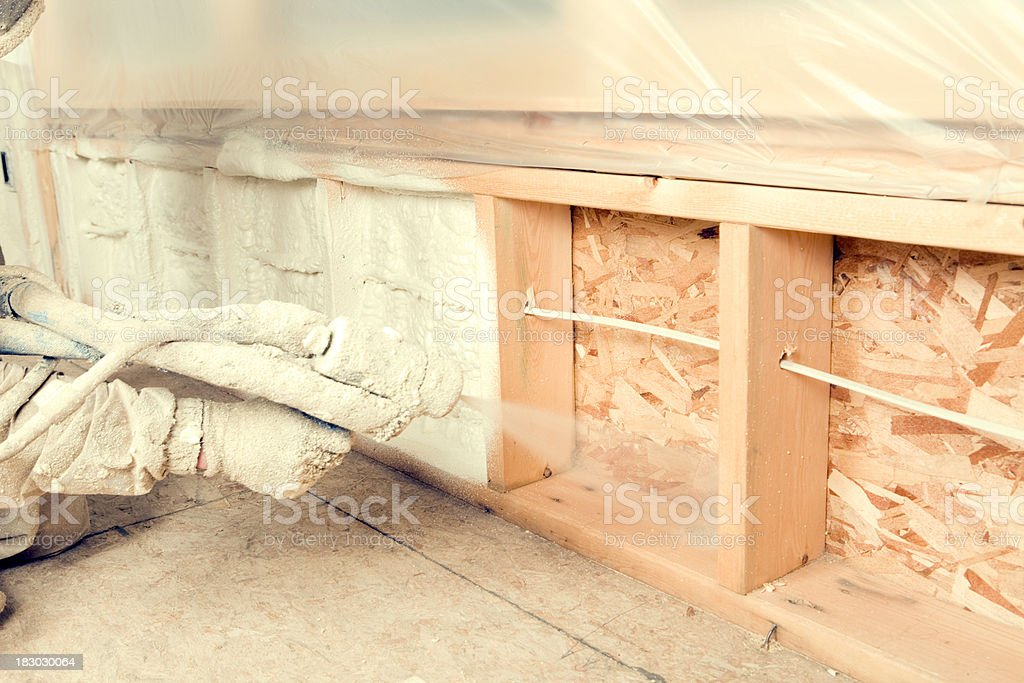 Construction Worker Spraying Expandable Foam Insulation Between stock photo