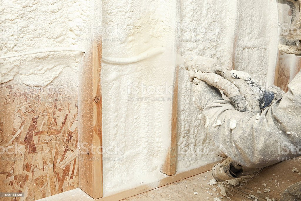 Construction Worker Spraying Expandable Foam Insulation between Wall Studs royalty-free stock photo