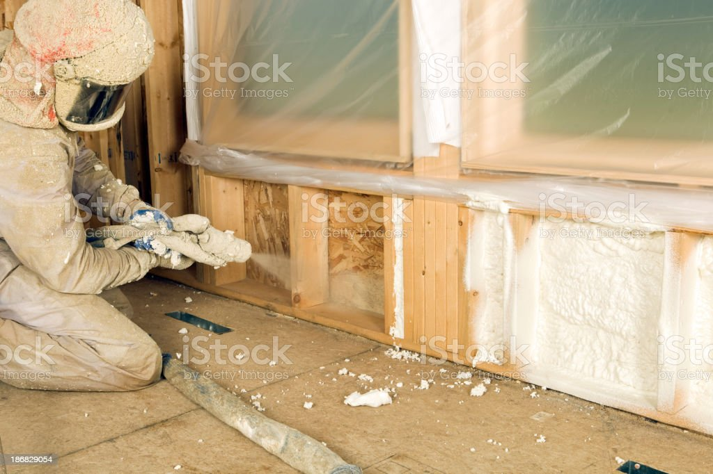 Construction Worker Spraying Expandable Foam Insulation between Wall Studs stock photo