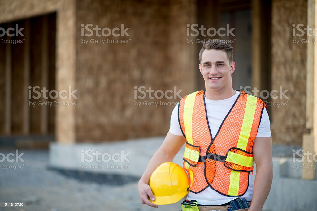 Construction Worker Standing by a New Home stock photo