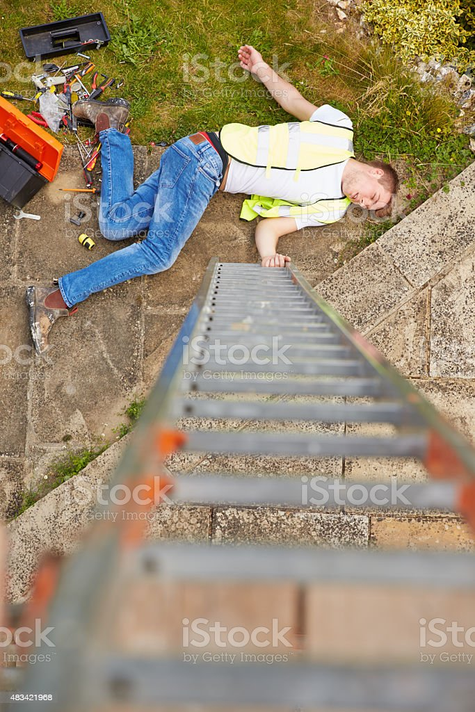 Construction Worker Suffering Injury After Fall From Ladder stock photo