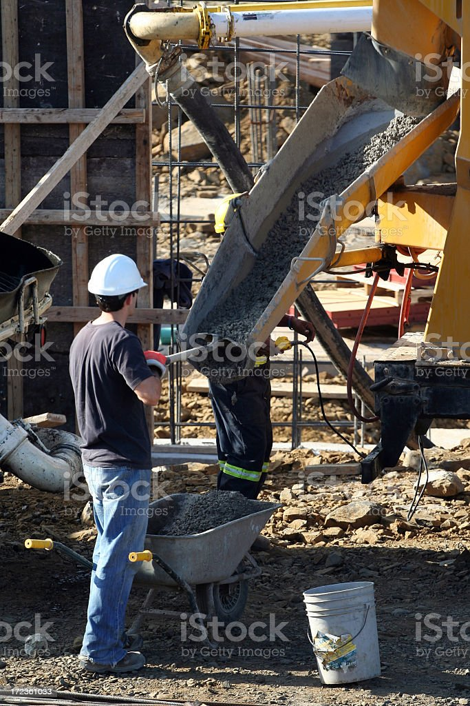 Construction worker supervising the pouring concrete machine stock photo
