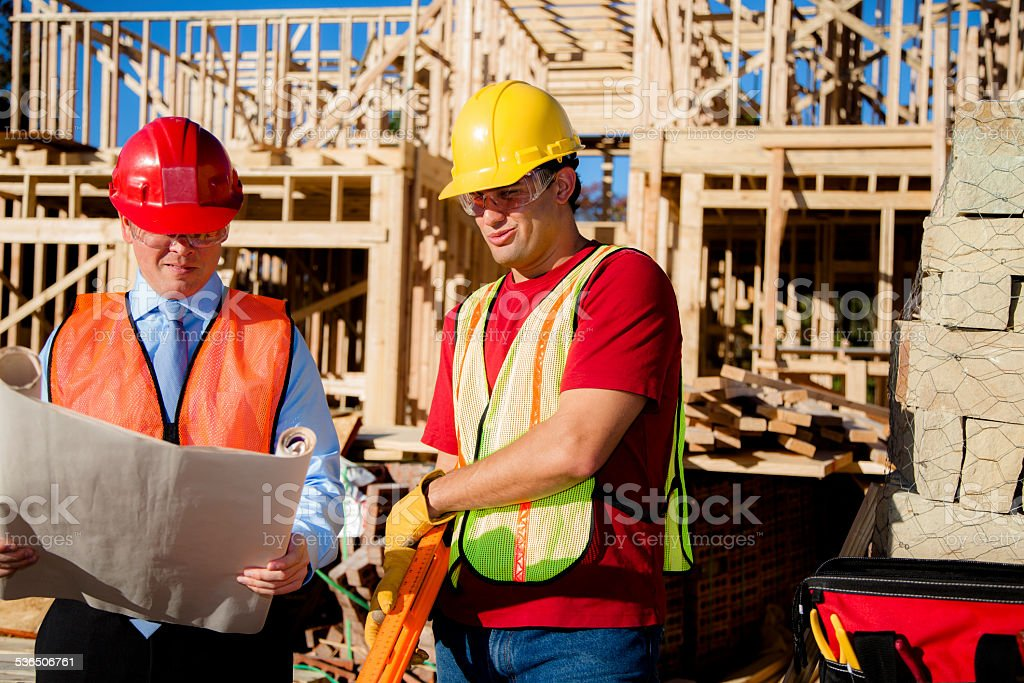 Construction worker, supervisor discuss blueprints at work site. Building. stock photo