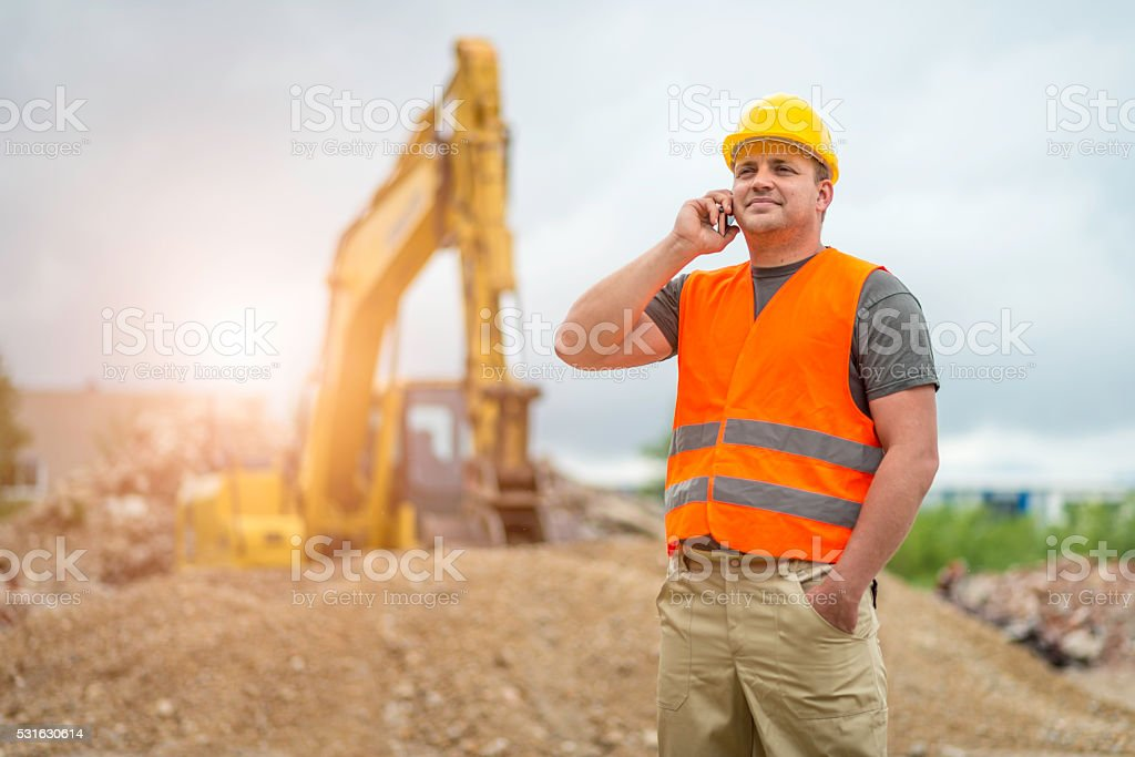 Construction worker takes a call stock photo