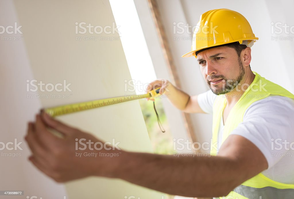 Construction worker taking measurements stock photo