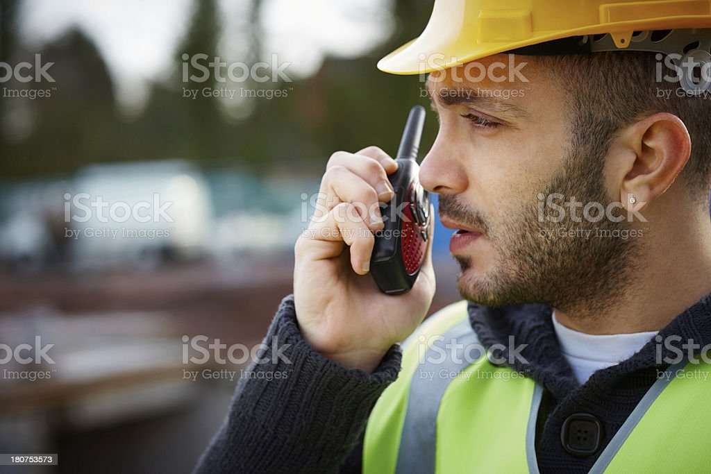 Construction worker talking into two way radio stock photo