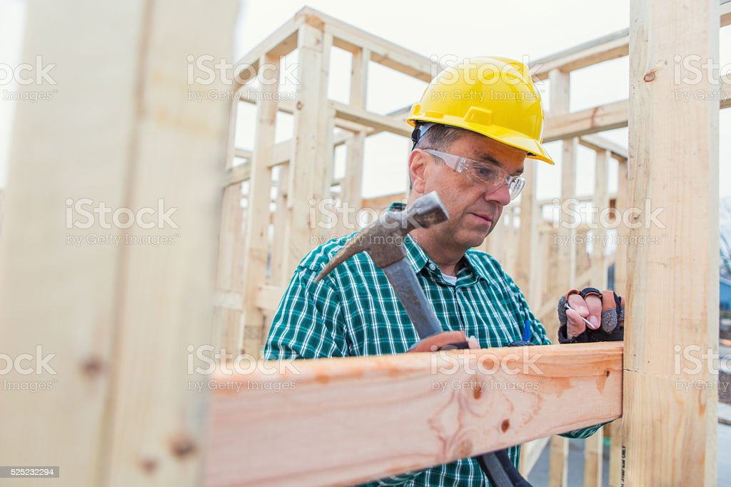 Construction worker uses hammer at job site stock photo